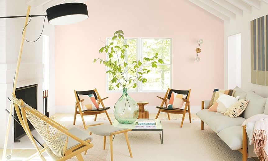 Bright, airy living room with pale pink accent wall painted with Benjamin Moore First Light
