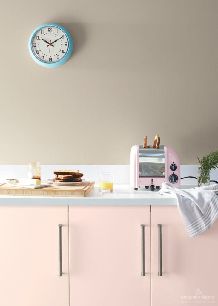 Sleek, modern kitchen with pale pink cabinets, wall painted in Benjamin Moore Thunder and pastel blue wall clock