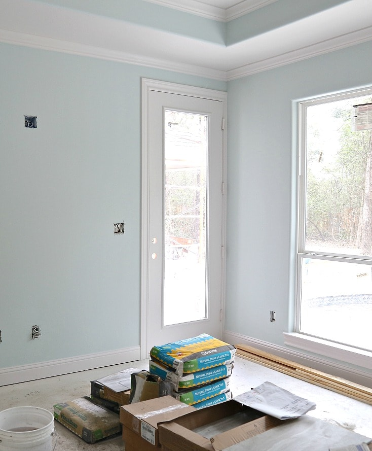 A room with lots of windows and natural light with pale aqua walls and trim color Simply White by Benjamin Moore.
