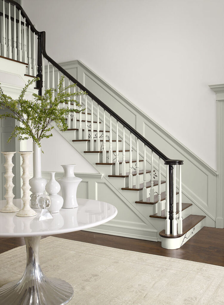 Staircase with white walls and wainscotting and trim Stonington Gray by Benjamin Moore.