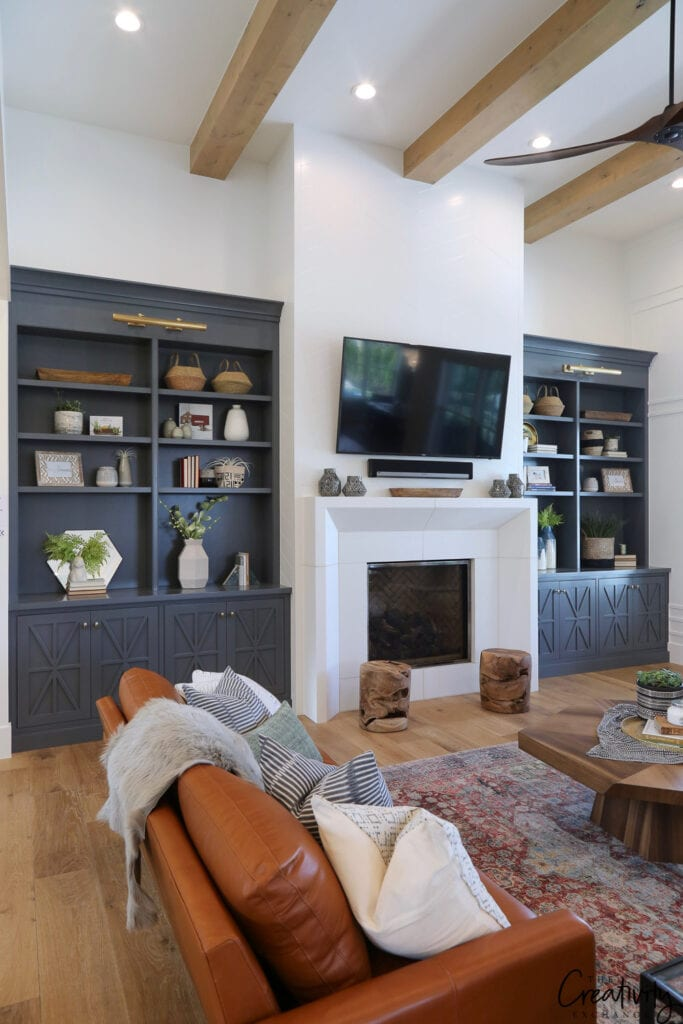 TV room with white walls and fireplace and built in bookcases painted in Trout Gray by Benjamin Moore.