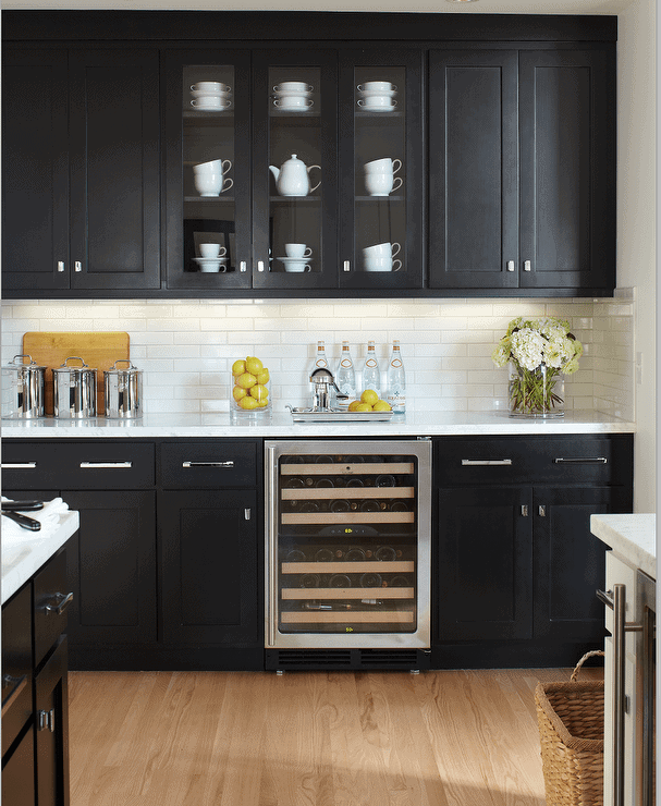 Black kitchen cabinets against white subway tile backsplash, featuring glass door cabinets and built-in wine fridge. Kitchen cabinet paint color: Black by Benjamin Moore.