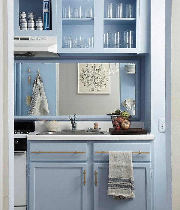 Pale blue kitchen cabinets and open shelving with glasses on display make for a retro kitchen look. Kitchen cabinet paint color: Blue Ice by Benjamin Moore.