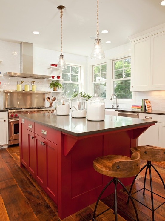 Rich red kitchen island with gray countertop stands out in a white and stainless steel kitchen. Kitchen cabinet paint color: Caliente by Benjamin Moore.