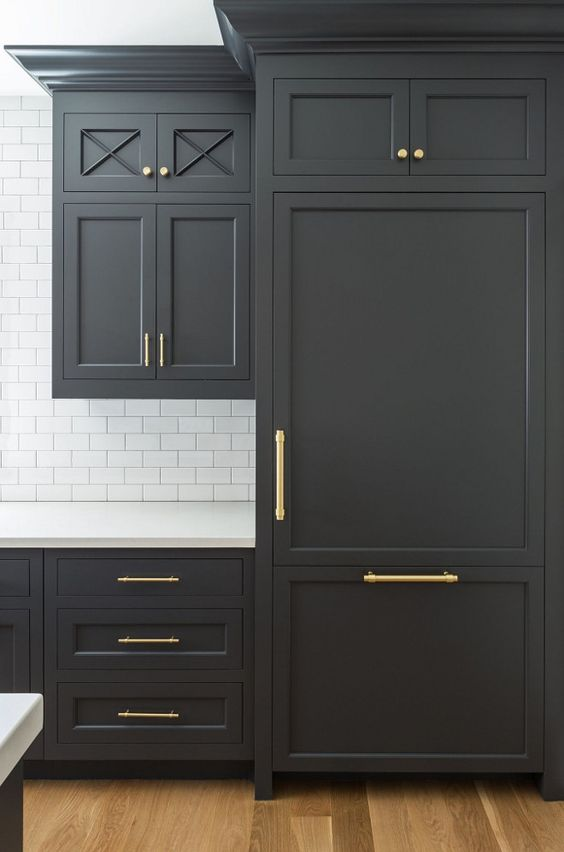 Beautiful matte dark gray kitchen cabinets with gold hardware against white subway tile backsplash. Kitchen cabinet paint color: Cheating Heart by Benjamin Moore.