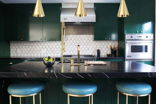 Glossy, deep green kitchen cabinets look stunning with brushed gold accents and a black marble countertop. Kitchen cabinet paint color: Chrome Green by Benjamin Moore.