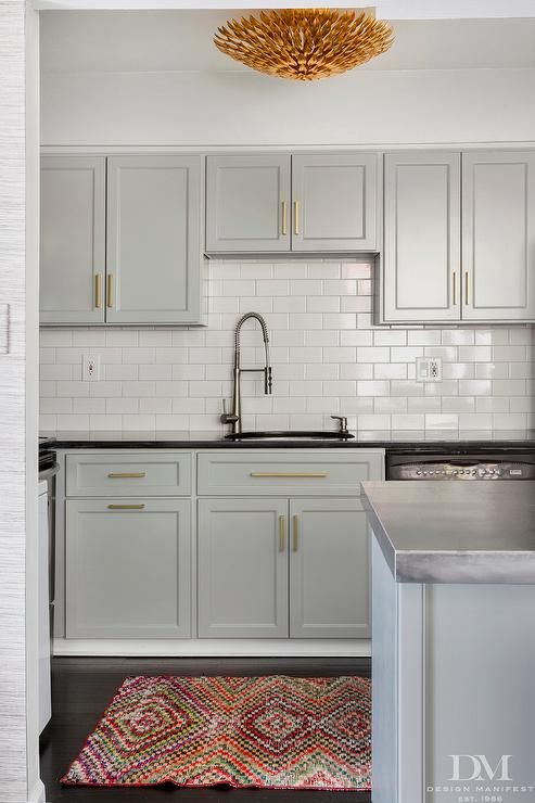 Creamy, light gray kitchen cabinets with gold white hardware compliment classic white subway tile. A colorful rug adds a splash of color. Kitchen cabinet paint color: Coventry Gray by Benjamin Moore.