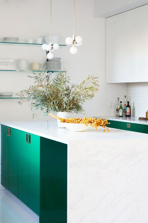 Vibrant, jade lower kitchen cabinets look stunning against stark white marble countertops and white walls. Kitchen cabinet paint color: Emerald Isle by Benjamin Moore.