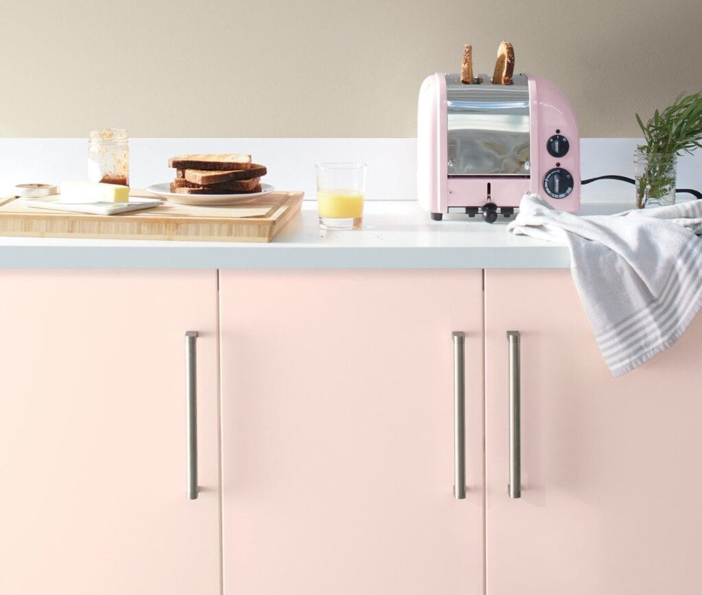 Pale pink cabinets in a modern, minimalist kitchen featuring a vintage pink toaster and almond colored walls. Kitchen cabinet paint color: First Light by Benjamin Moore.