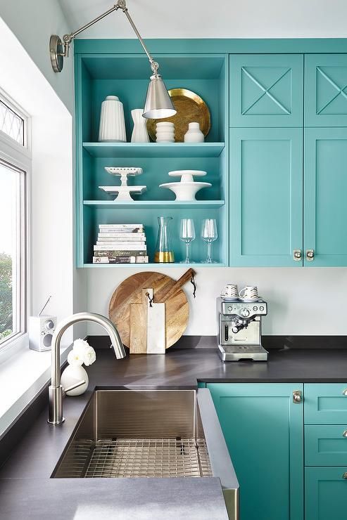 Cheery teal blue cabinets with a dark gray countertop. Open shelving displays styled kitchen items. Kitchen cabinet paint color: Florida Key's Blue by Benjamin Moore.