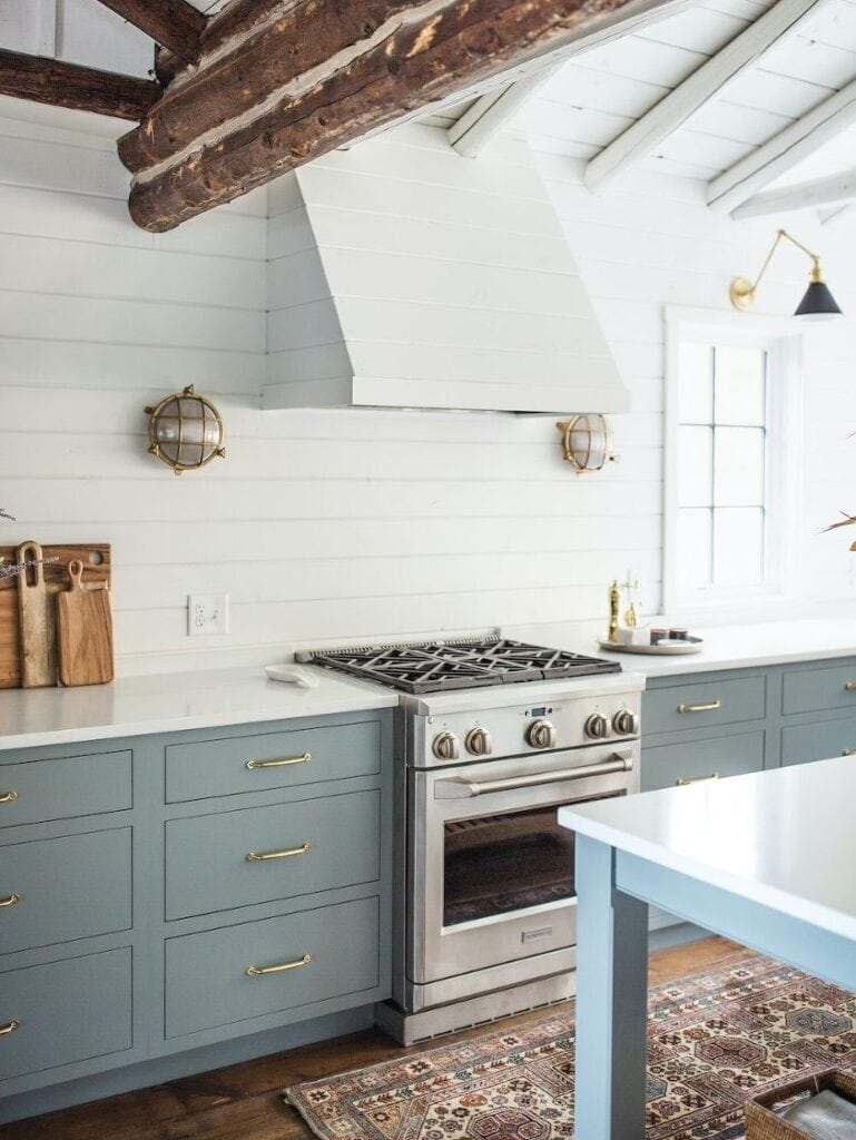 Cool blue-gray cabinets with gold hardware look inviting with a white countertop and white shiplap walls. Kitchen cabinet paint color: Gibraltar Cliffs by Benjamin Moore.