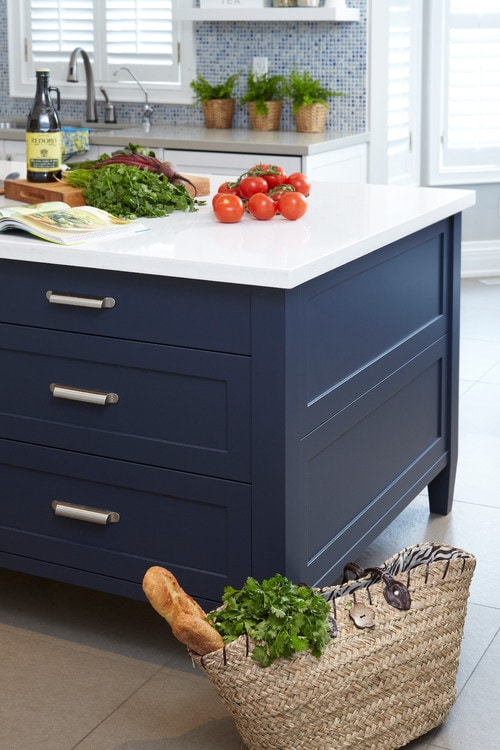 A navy blue kitchen island looks sophisticated against a white countertop. Fresh vegetables sit ready to be chopped. Kitchen island paint color: Hale Navy by Benjamin Moore.