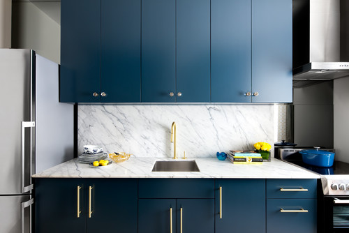 Sleek, modern sapphire blue kitchen cabinets contrast with white marble countertops and backsplash and gold hardware. Kitchen cabinet paint color: New York State of Mind by Benjamin Moore.