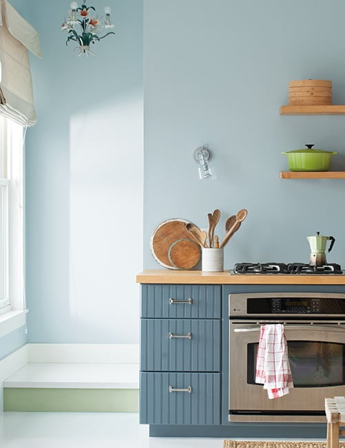 Cheery blue cabinets pair beautifully with blue walls in a minimalist kitchen. Cabinet paint color: Normandy by Benjamin Moore.
