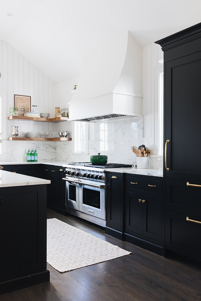 Stunning black kitchen cabinets with gold hardware contrast against stark white walls and white marble backsplash. Kitchen cabinet paint color: Onyx by Benjamin Moore.