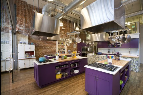 Plum-colored kitchen cabinets pop in an urban industrial loft kitchen with stainless steel ranges overhead. Kitchen cabinet paint color: Passion Plum by Benjamin Moore.