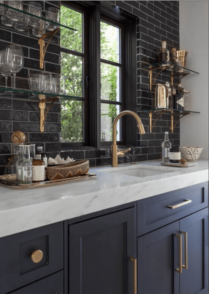 Dark gray/navy kitchen cabinets with brushed gold hardware contrast with a white marble countertop and glossy black subway tile. Kitchen cabinet paint color: Raccoon Fur by Benjamin Moore.