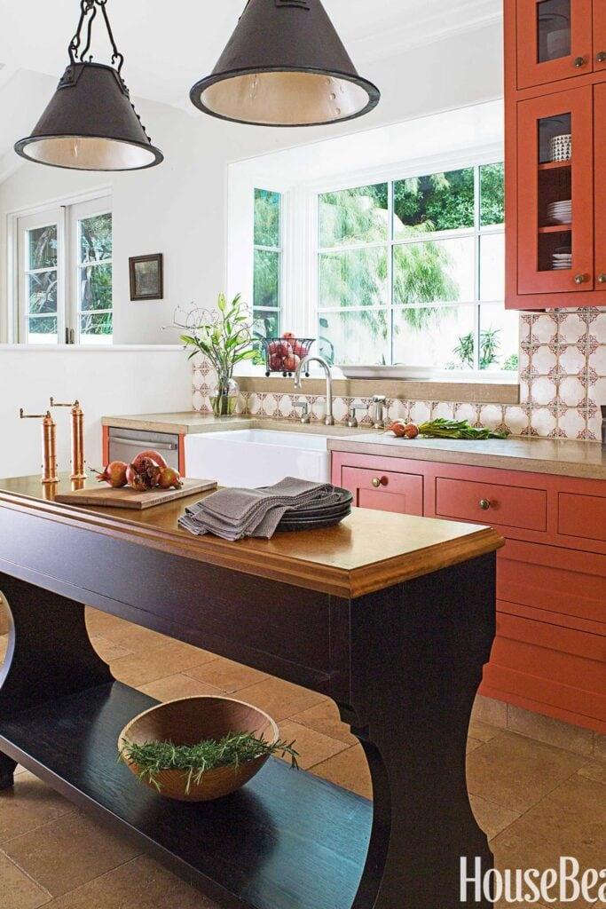 Burnt orange kitchen cabinets look warm against vintage Spanish tile backsplash and big windows. Kitchen cabinet paint color: Salsa Dancing by Benjamin Moore.