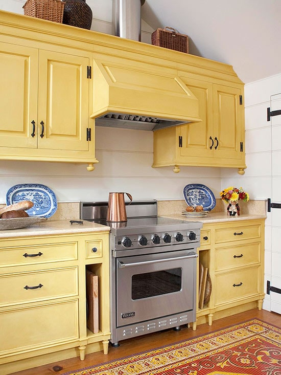 Buttery yellow kitchen cabinets make for a warm, country kitchen vibe. Kitchen cabinet paint color: Sweet Butter by Benjamin Moore.