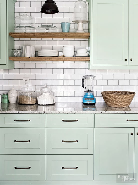 Pale mint green cabinets softly glow against white subway tile backsplash and natural wood open shelving. Kitchen cabinet paint color: Tea Light by Benjamin Moore.
