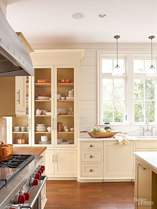 Soft, pale yellow cabinets with mesh open doors look traditional and inviting against white shiplap walls. Kitchen cabinet paint color: Twisted Oak Path by Benjamin Moore.