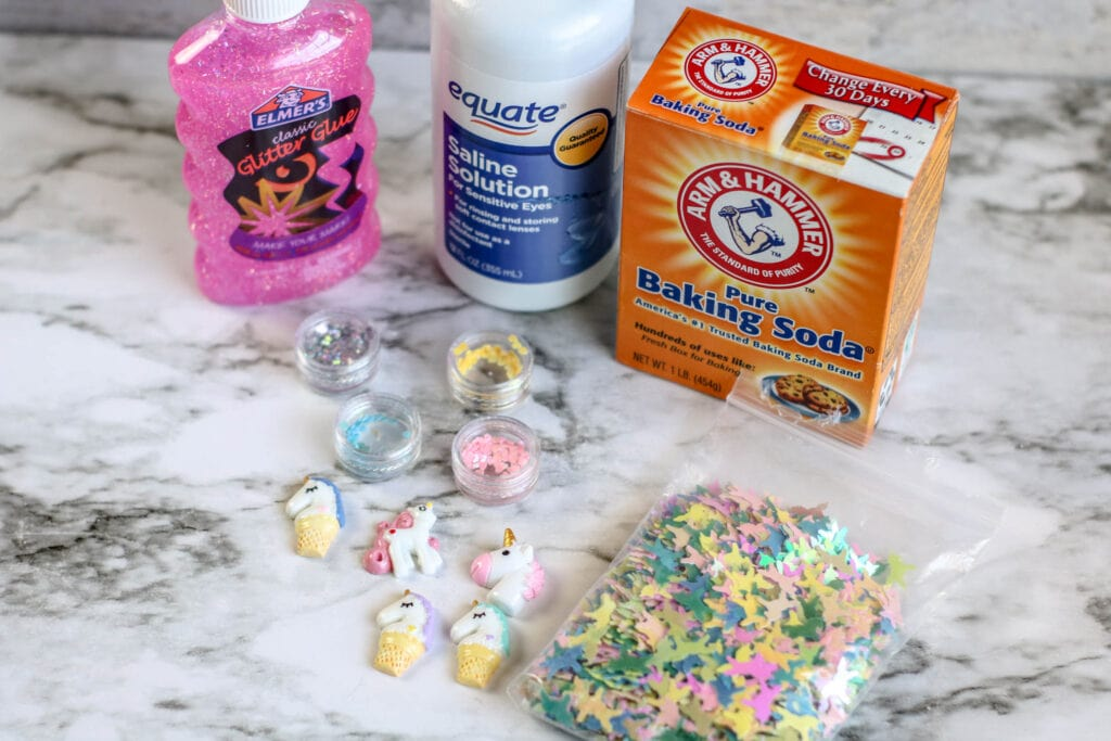 Ingredients to make DIY unicorn slime: Elmer's pink glitter glue, saline solution, baking soda, glitter, confetti and unicorn toys.