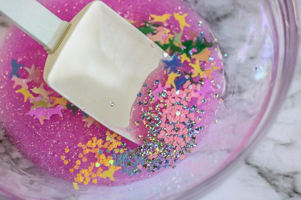 Adding glitter and confetti to make pink glitter unicorn slime.