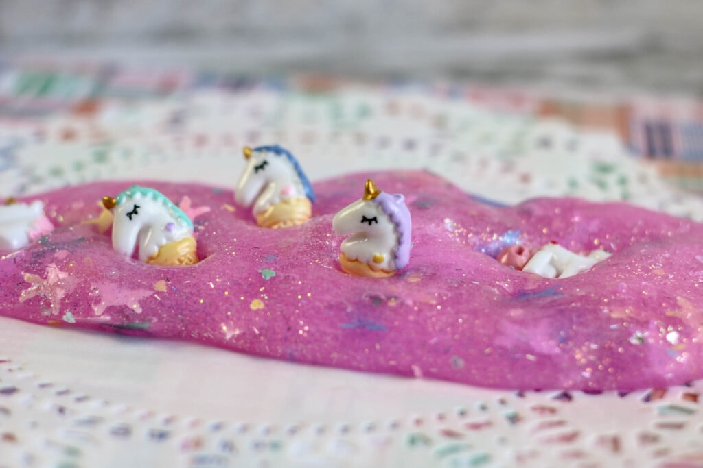 Pink glitter unicorn slime with small unicorn toys.