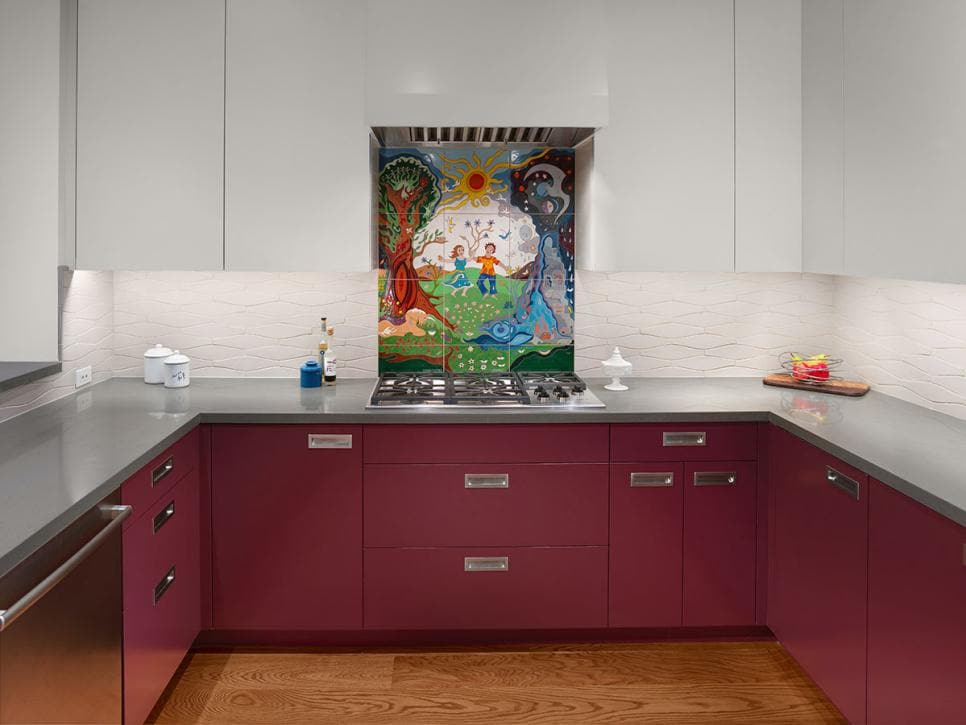 Modern, wine-colored kitchen lower cabinets look inviting against gray countertops, white backsplash and pale gray upper cabinets.