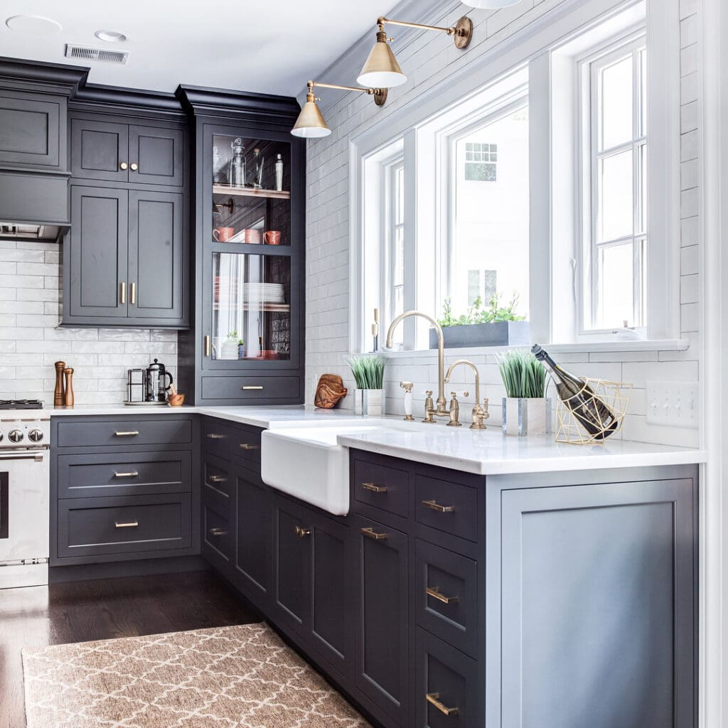 Dark gray, almost black kitchen cabinets in a crisp, clean, bright white kitchen. Kitchen cabinet paint color: Wrought Iron by Benjamin Moore.