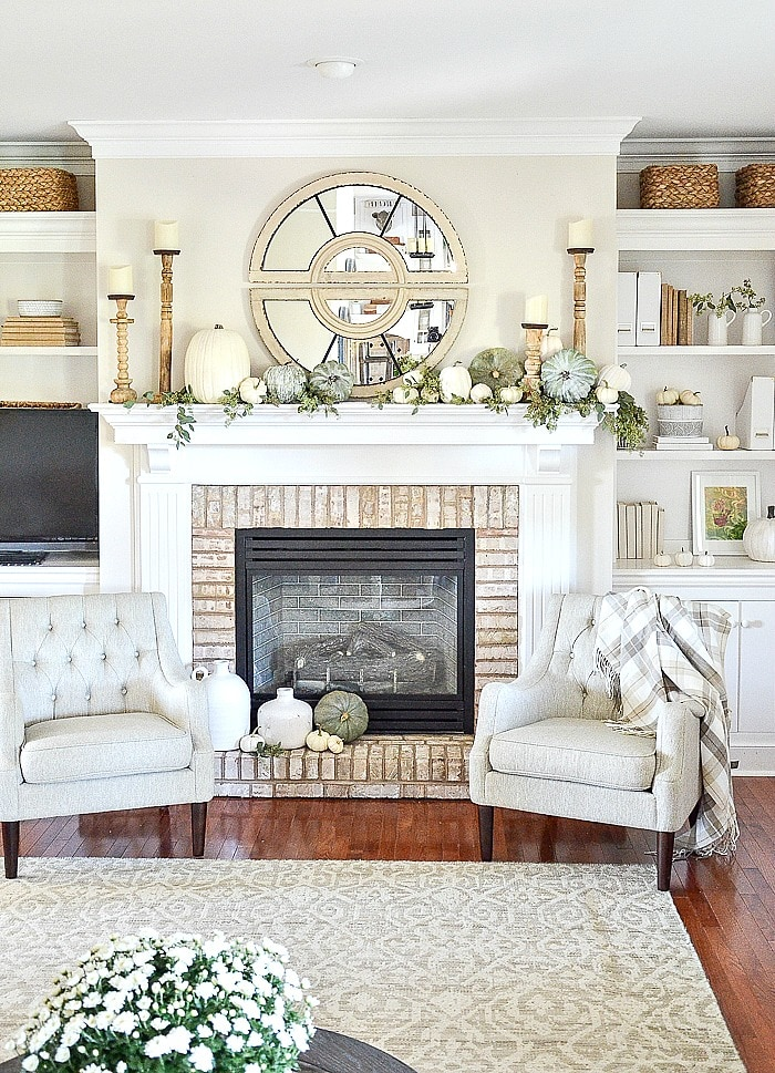 A white and green mantel decorated for fall