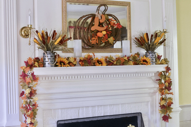 A fall mantel decorated with leaves and cat tails