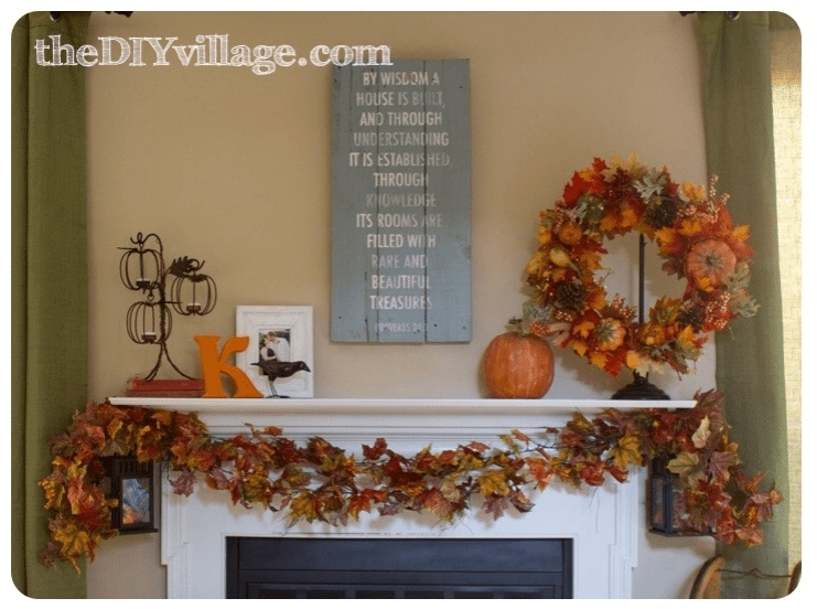 A mantel with a garland of orange leaves and a wreath with leaves and orange pumpkins