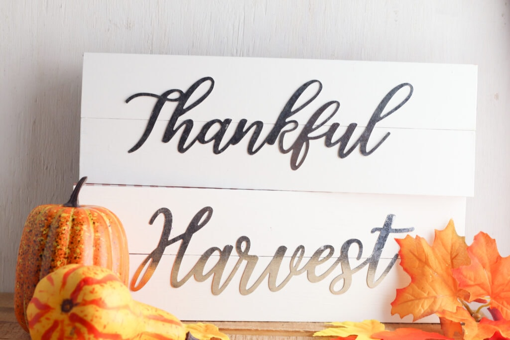 DIY Metal Word Signs made with Dollar Tree inspirational wall words. DIY fall decor paired with decorative pumpkins and faux leaves.