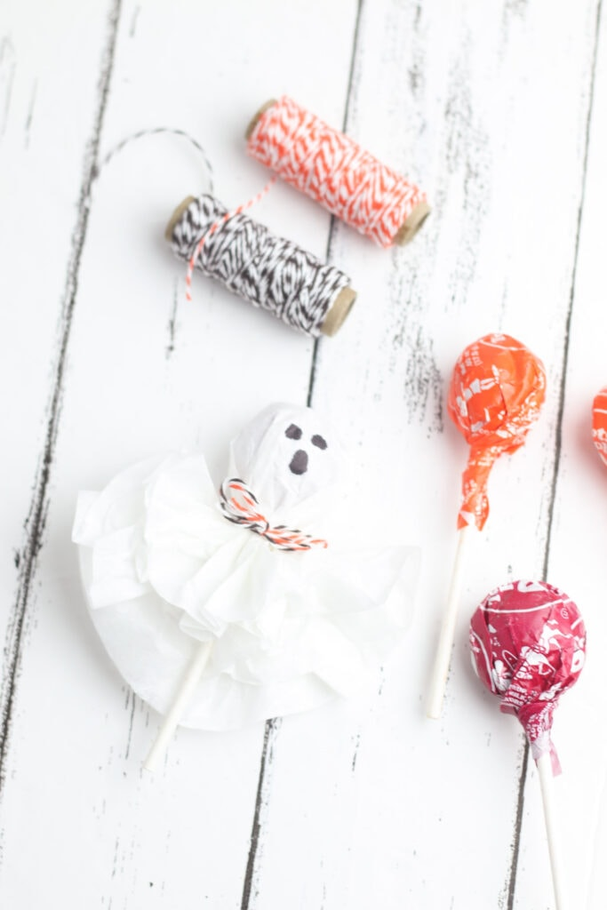 A finished ghost lollipop made from coffee filters, Tootsie pops and twine.