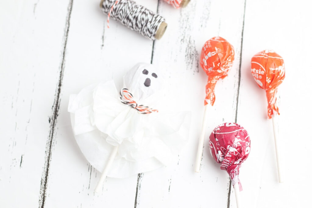 Supplies needed to make ghost lollipops: Tootsie Pops, coffee filters, twine and black marker.