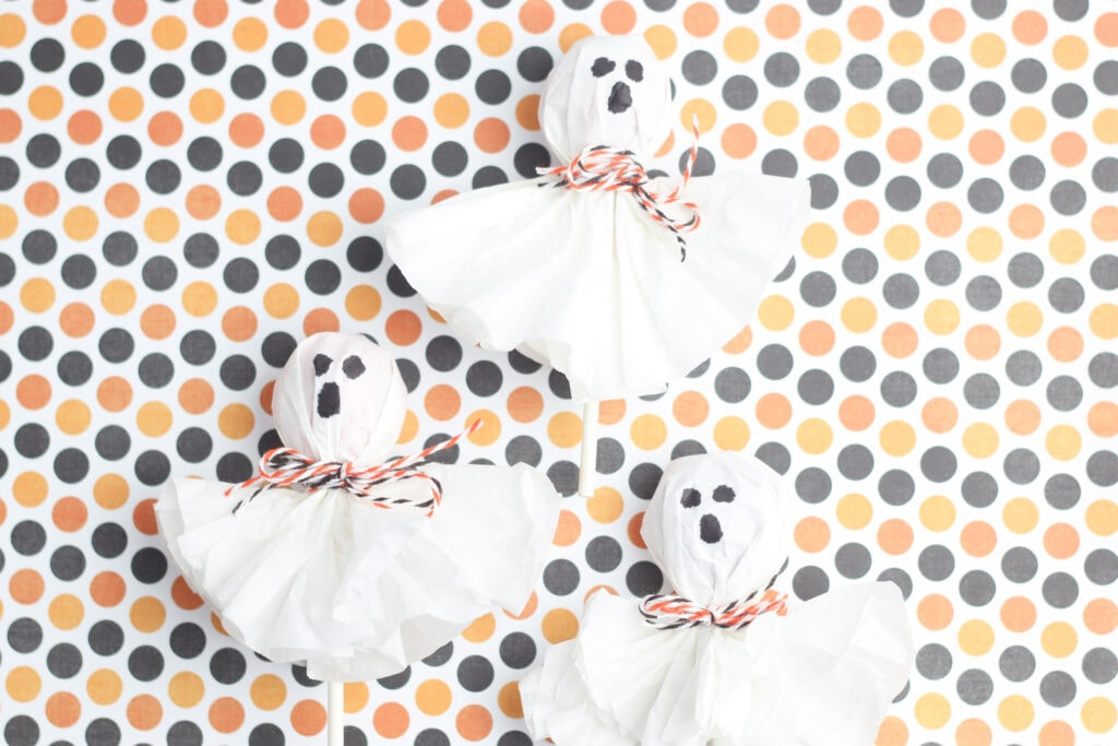 Ghost lollipops made from Tootsie Pops, coffee filters and twine against a Halloween polka dot color scheme.