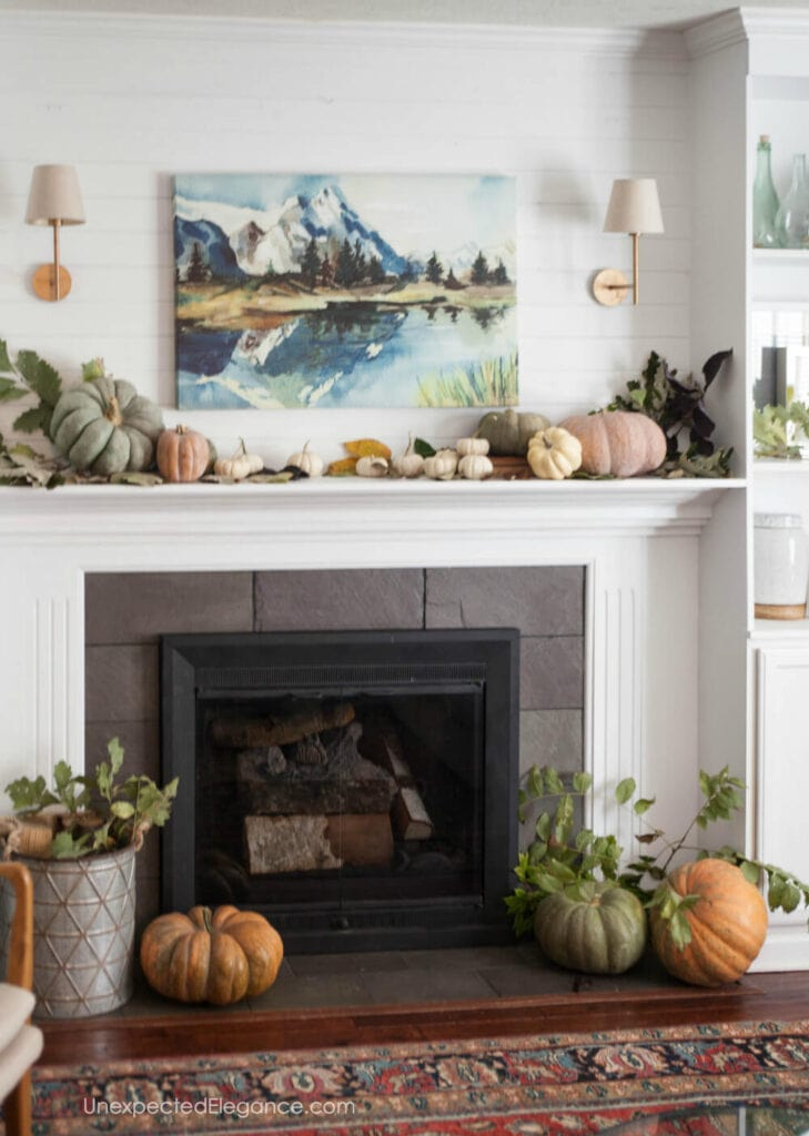 A fall mantel with a painting of mountains and a shelf of pumpkins and squash.