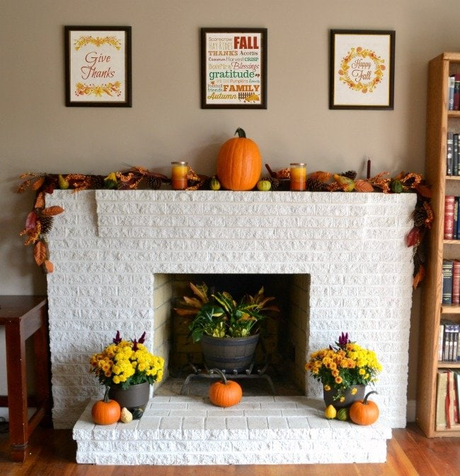 Bright orange and yellow fall mantel with printable wall art in black frames