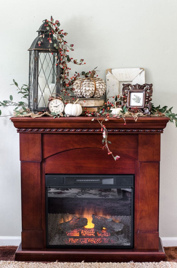 The top of a small electric fireplace decorated for fall
