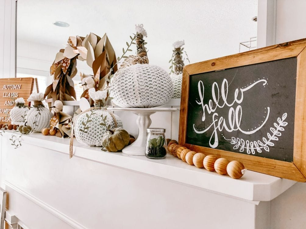 """A chalkboard that says """"Hellow Fall"""" on a mantel with fabric pumpkins"""