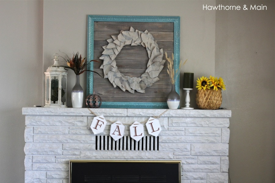 A fireplace mantel decorated for fall with a banner that reads FALL