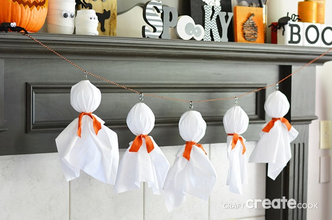 White ghost with orange bow tie garland hanging from a Halloween-styled mantle: Great DIY Halloween decoration ideas.