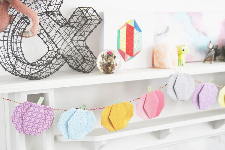 Here's a pretty idea for DIY decor for Halloween: pastel origami paper pumpkin garland hanging on a mantle.