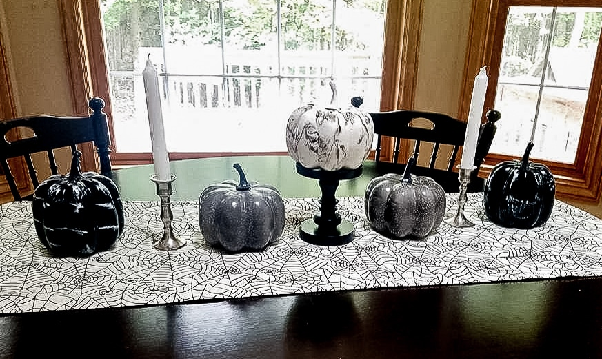 Spiderweb table runner styled with black, gray and white pumpkins and candlesticks is an easy DIY Halloween decor idea.