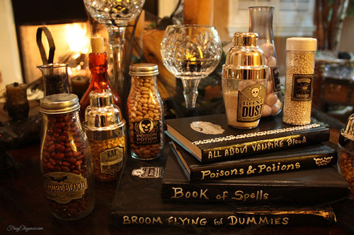 Halloween table display with books and DIY potion bottles.