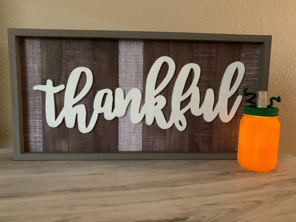 Lighted mason jar pumpkin craft next to a wooden Thankful fall decor sign.