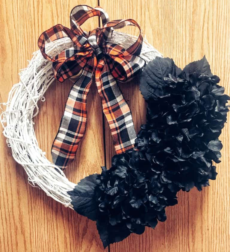 Pretty fall white wooden decor wreath decorated with black fabric flowers and orange and black plaid bow.