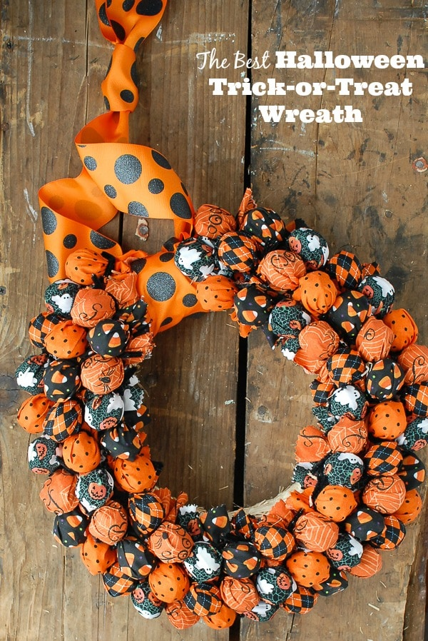 DIY Halloween Trick or Treat wreath with hidden candy in black and orange colors.