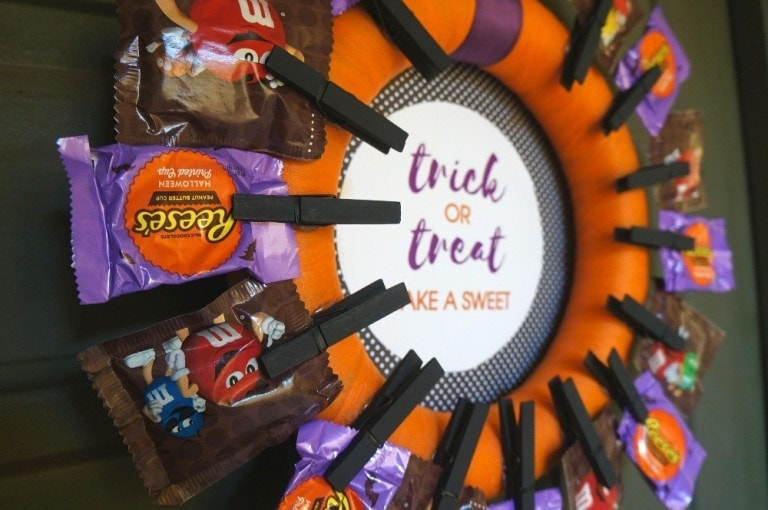 DIY Halloween Trick or Treat wreath with candy clipped to it using black painted clothespins.